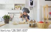 Купить «Happy little girl chef mixing the dough with big wooden spoon in glass bowl», фото № 28581037, снято 19 июля 2018 г. (c) Константин Шишкин / Фотобанк Лори