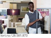 Assistant male is standing near modern furniture. Стоковое фото, фотограф Яков Филимонов / Фотобанк Лори