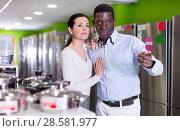 Купить «Couple standing in store of household appliances», фото № 28581977, снято 21 февраля 2018 г. (c) Яков Филимонов / Фотобанк Лори