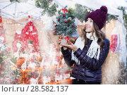 Купить «Customer choosing Christam tree outdoor in evening», фото № 28582137, снято 22 декабря 2016 г. (c) Яков Филимонов / Фотобанк Лори