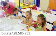 Купить «Glad kids drawing on lesson in elementary school class with help of teacher», видеоролик № 28585733, снято 7 сентября 2016 г. (c) Яков Филимонов / Фотобанк Лори
