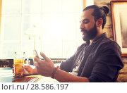 Купить «man with smartphone drinking beer at bar or pub», фото № 28586197, снято 2 июня 2016 г. (c) Syda Productions / Фотобанк Лори