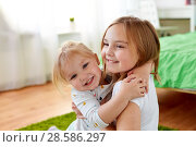 Купить «happy little girls or sisters hugging at home», фото № 28586297, снято 15 октября 2017 г. (c) Syda Productions / Фотобанк Лори