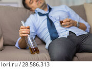 close up of man sleeping with bottle of alcohol. Стоковое фото, фотограф Syda Productions / Фотобанк Лори
