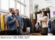 Купить «friends photographing at vintage clothing store», фото № 28586321, снято 30 ноября 2017 г. (c) Syda Productions / Фотобанк Лори