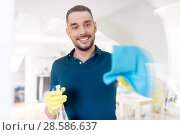 Купить «man in rubber gloves cleaning window with rag», фото № 28586637, снято 10 мая 2018 г. (c) Syda Productions / Фотобанк Лори
