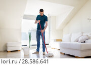 Купить «man with mop and bucket cleaning floor at home», фото № 28586641, снято 10 мая 2018 г. (c) Syda Productions / Фотобанк Лори