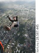 Купить «Парашютист в свободном полёте, выпрыгнувший спиной вниз с вертолёта Ми-8 над городом Петрозаводском. Карелия», эксклюзивное фото № 28587445, снято 8 июня 2018 г. (c) Сергей Цепек / Фотобанк Лори