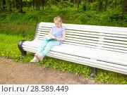 Купить «Girl is sitting on a bench and reading a book», фото № 28589449, снято 11 июня 2017 г. (c) Сергей Дубров / Фотобанк Лори