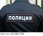 """Полицейский. Нашивка на спине """"Полиция"""" (2018 год). Редакционное фото, фотограф Victoria Demidova / Фотобанк Лори"""
