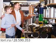 Купить «Father and teenage son examining drum units in guitar shop», фото № 28590353, снято 29 марта 2017 г. (c) Яков Филимонов / Фотобанк Лори