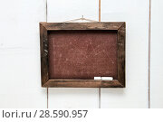 Купить «Школьная доска без надписи висит на деревянной стене», фото № 28590957, снято 16 июня 2018 г. (c) Наталья Осипова / Фотобанк Лори