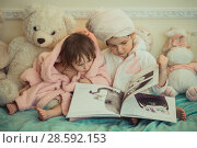 Купить «Little sisters in plush robe riding the book», фото № 28592153, снято 20 февраля 2017 г. (c) Julia Shepeleva / Фотобанк Лори