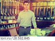 Купить «Male seller offering necessary hunting equipments», фото № 28592845, снято 11 декабря 2017 г. (c) Яков Филимонов / Фотобанк Лори