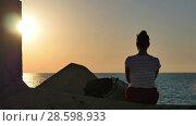 Купить «Young woman sitting on the rocks and looking at the sunset sea», видеоролик № 28598933, снято 13 июня 2017 г. (c) Vasily Alexandrovich Gronskiy / Фотобанк Лори