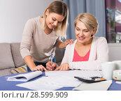 Купить «Daughter helps mother to lead home accounting», фото № 28599909, снято 13 ноября 2017 г. (c) Яков Филимонов / Фотобанк Лори