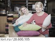 Купить «joyous young and senior female customers looking through pillows in textile shop», фото № 28600105, снято 15 февраля 2017 г. (c) Яков Филимонов / Фотобанк Лори