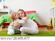 Купить «happy little girls or sisters hugging at home», фото № 28605677, снято 15 октября 2017 г. (c) Syda Productions / Фотобанк Лори