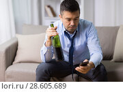 Купить «man with smartphone and bottle of alcohol at home», фото № 28605689, снято 24 ноября 2017 г. (c) Syda Productions / Фотобанк Лори