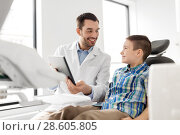 Купить «dentist showing tablet pc to kid patient at clinic», фото № 28605805, снято 22 апреля 2018 г. (c) Syda Productions / Фотобанк Лори