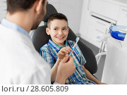 Купить «dentist giving toothbrush to kid patient at clinic», фото № 28605809, снято 22 апреля 2018 г. (c) Syda Productions / Фотобанк Лори