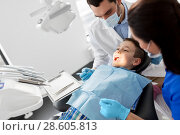 Купить «dentist checking for kid teeth at dental clinic», фото № 28605813, снято 22 апреля 2018 г. (c) Syda Productions / Фотобанк Лори