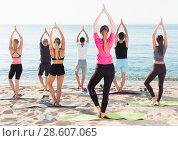 Купить «Sporty people practicing yoga on beach», фото № 28607065, снято 14 июня 2017 г. (c) Яков Филимонов / Фотобанк Лори
