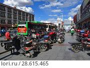 Купить «Тибет, виды города Лхаса. Много мотоциклов и мопедов припарковано на одной из центральных улиц», фото № 28615465, снято 2 июня 2018 г. (c) Овчинникова Ирина / Фотобанк Лори