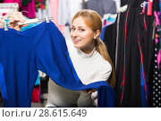 Купить «Girl choosing a trousers in sport store», фото № 28615649, снято 17 августа 2018 г. (c) Яков Филимонов / Фотобанк Лори