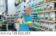 Купить «Positive man with dog looking new bowl in pet store, woman on background», видеоролик № 28622253, снято 24 мая 2018 г. (c) Яков Филимонов / Фотобанк Лори