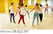 Купить «Group of children with their teacher holding hands and dancing in circle in dance school», видеоролик № 28622297, снято 26 марта 2018 г. (c) Яков Филимонов / Фотобанк Лори