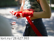 Купить «Athletic caucasian woman boxer wrapping hands with bandages for workout in summer park», фото № 28627993, снято 18 июня 2018 г. (c) Константин Шишкин / Фотобанк Лори