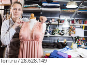 Купить «Female seamstress is thinking about new dress for collection of clothes near mannequin», фото № 28628149, снято 5 мая 2018 г. (c) Яков Филимонов / Фотобанк Лори