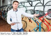 Купить «Smiling man is choosing modern bicycle with bike characteristic in the bike store.», фото № 28628369, снято 14 мая 2018 г. (c) Яков Филимонов / Фотобанк Лори