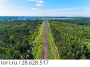 Купить «A railway track passing through the forest and field.», фото № 28628517, снято 15 июня 2018 г. (c) Андрей Радченко / Фотобанк Лори