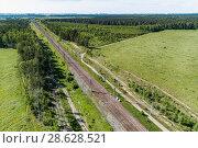 Купить «A railway track passing through the forest and field.», фото № 28628521, снято 15 июня 2018 г. (c) Андрей Радченко / Фотобанк Лори