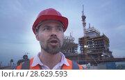 Купить «Man in a helmet, architect, engineer, manager tells about the progress of construction in evening stock footage video», видеоролик № 28629593, снято 23 июня 2018 г. (c) Юлия Машкова / Фотобанк Лори