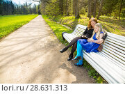 Купить «Blonde school-aged girl with mother sit on a bench and read a book», фото № 28631313, снято 21 мая 2017 г. (c) Сергей Дубров / Фотобанк Лори