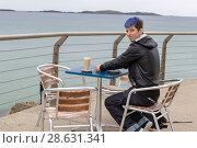 Купить «Young man drinking cofee at seaside», фото № 28631341, снято 1 июля 2017 г. (c) Ольга Марк / Фотобанк Лори