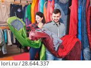 Купить «Smiling couple examining various sleeping bags», фото № 28644337, снято 8 марта 2017 г. (c) Яков Филимонов / Фотобанк Лори