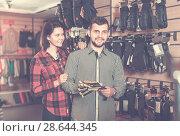 Купить «Couple demonstrate selected gloves for tourism», фото № 28644345, снято 8 марта 2017 г. (c) Яков Филимонов / Фотобанк Лори