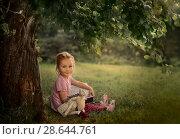 Купить «Маленькая девочка читает книгу в саду», фото № 28644761, снято 18 июня 2018 г. (c) Julia Shepeleva / Фотобанк Лори