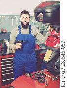 Купить «Positive male worker fixing failed scooter», фото № 28646057, снято 25 сентября 2018 г. (c) Яков Филимонов / Фотобанк Лори