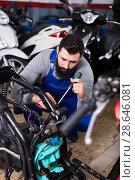 Купить «Worker repairing motorbike», фото № 28646081, снято 14 августа 2018 г. (c) Яков Филимонов / Фотобанк Лори