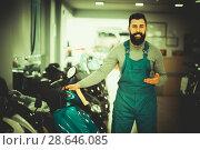 Купить «happy man worker displaying various motorcycles in workshop», фото № 28646085, снято 21 сентября 2019 г. (c) Яков Филимонов / Фотобанк Лори