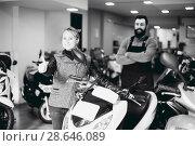 Купить «positive male worker assisting female customer in repairing motorcycle in workshop», фото № 28646089, снято 12 декабря 2018 г. (c) Яков Филимонов / Фотобанк Лори