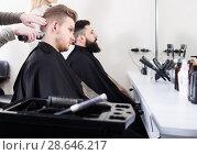 Купить «Glad male having their hair cut by hairdressers», фото № 28646217, снято 27 января 2017 г. (c) Яков Филимонов / Фотобанк Лори