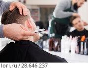 Купить «Adult man hairdresser making haircut to client», фото № 28646237, снято 27 января 2017 г. (c) Яков Филимонов / Фотобанк Лори