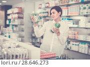Купить «Smiling female customer looking for products», фото № 28646273, снято 31 января 2017 г. (c) Яков Филимонов / Фотобанк Лори