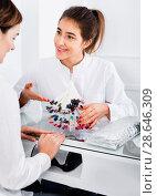Купить «Female manicurist showing lacquer color schemes», фото № 28646309, снято 2 февраля 2017 г. (c) Яков Филимонов / Фотобанк Лори